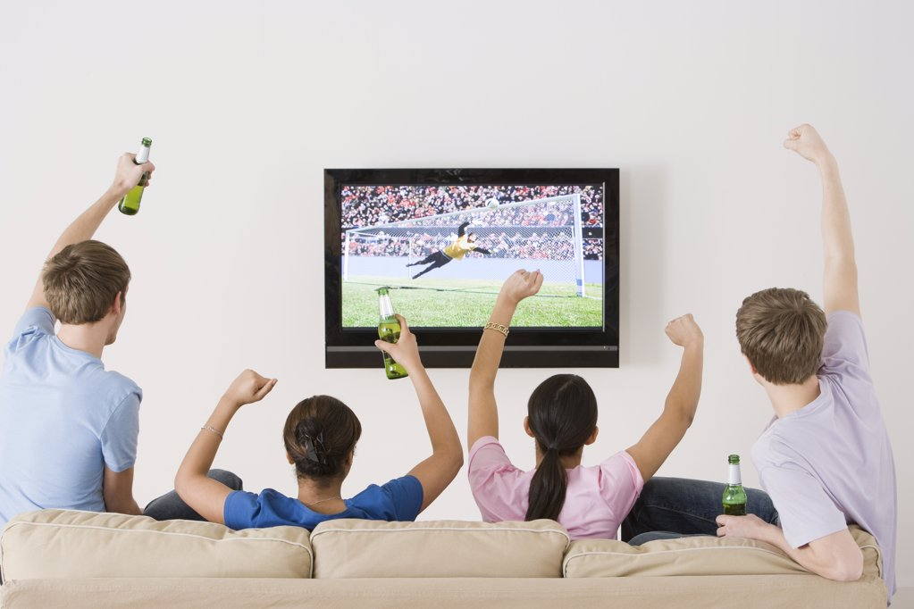 Stock Photo: 1439R-1090528 Friends watching football on the tv