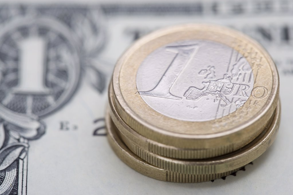 Euro coins on dollar bill : Stock Photo
