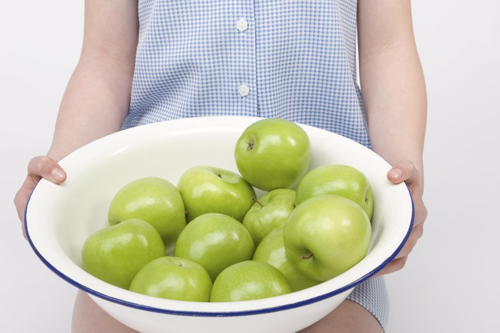 Stock Photo: 1439R-1093715 Girl with bowl of apples