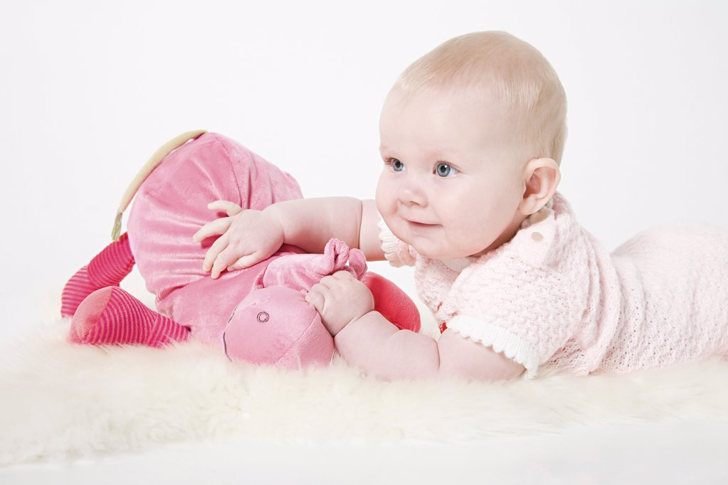 Baby girl holding a toy : Stock Photo