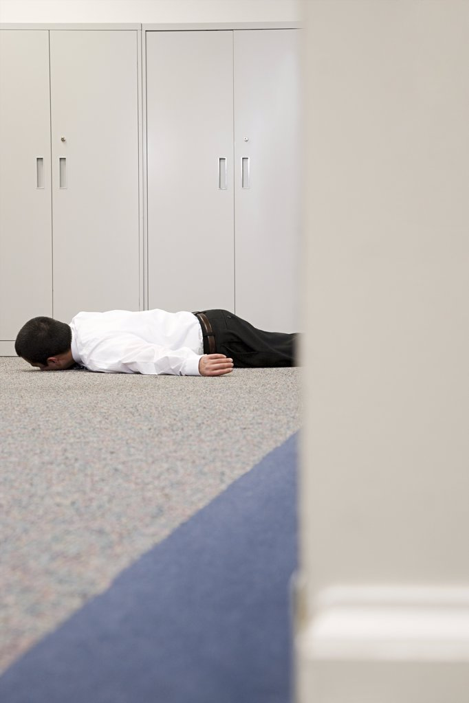 Stock Photo: 1439R-1097538 Man on floor of office