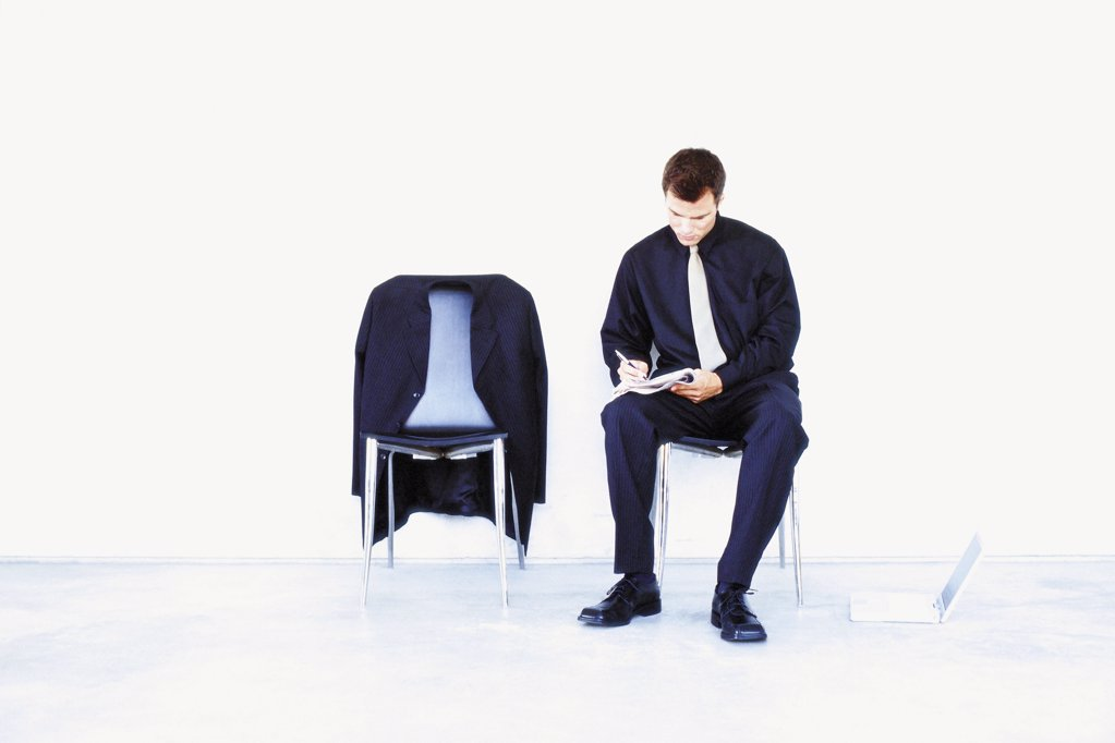 Stock Photo: 1439R-110060 Man sitting on chair writing notes