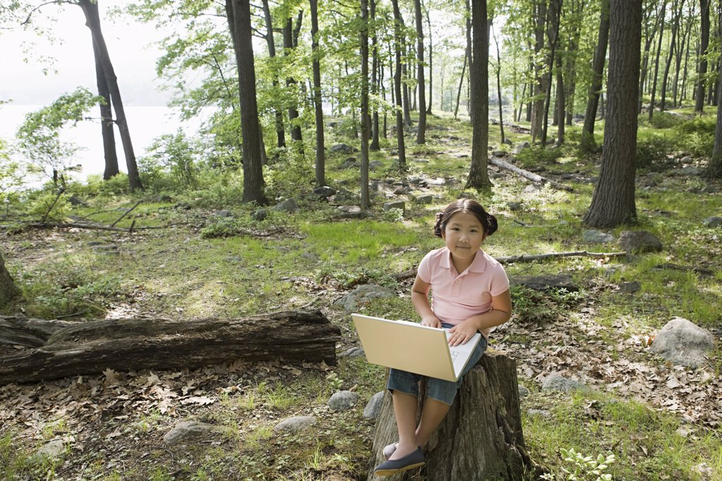 Stock Photo: 1439R-1100752 A girl using a laptop in a forest