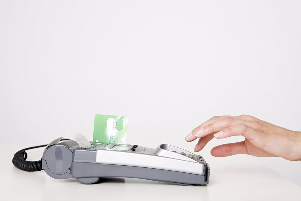 Woman using a chip and pin machine : Stock Photo
