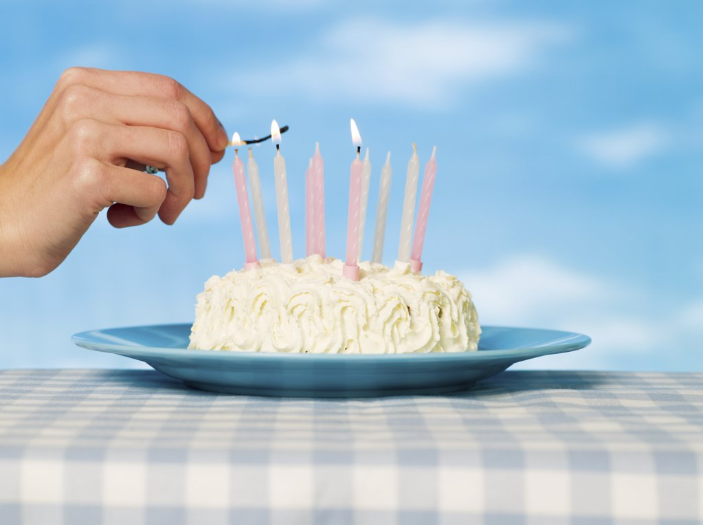 Stock Photo: 1439R-1101673 A person lighting matches on a cake