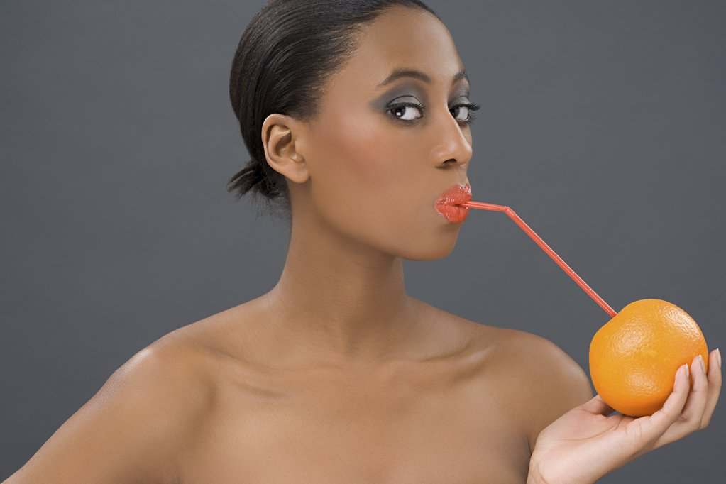 Woman drinking from an orange : Stock Photo