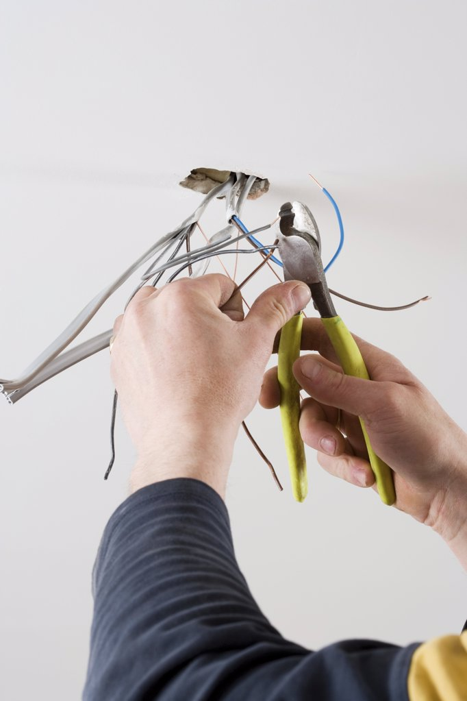 An electrician cutting wires : Stock Photo