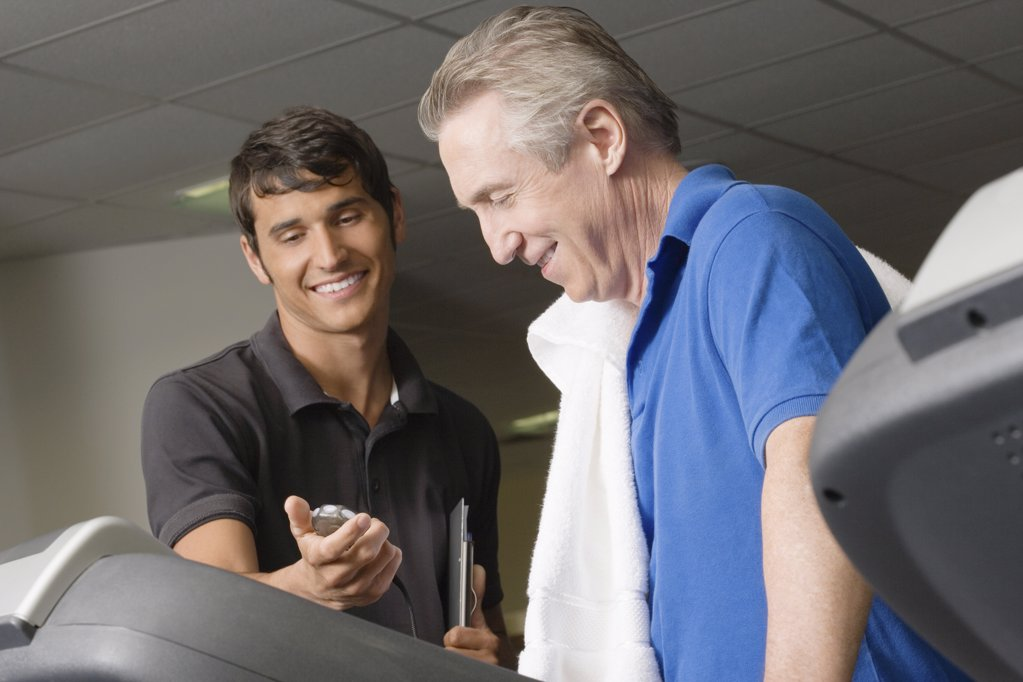 Stock Photo: 1439R-1107129 A personal trainer helping a man on a treadmill