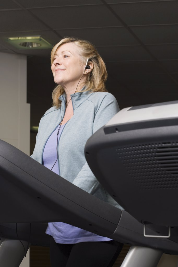 Stock Photo: 1439R-1107130 A mature woman listening to music whilst exercising