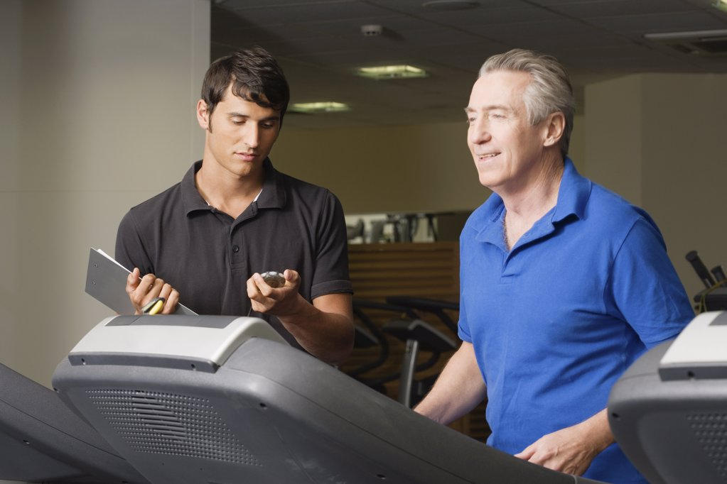 A personal trainer helping a man on a treadmill : Stock Photo