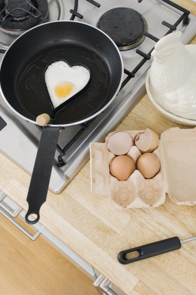 Fried egg in heart shape : Stock Photo