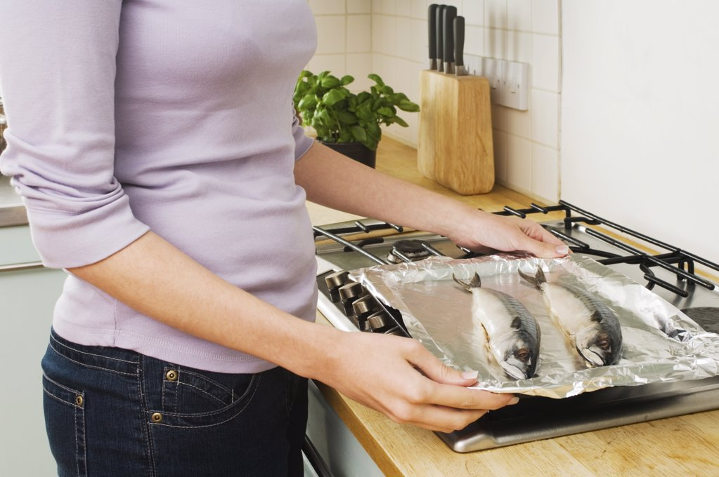 Woman cooking fish : Stock Photo