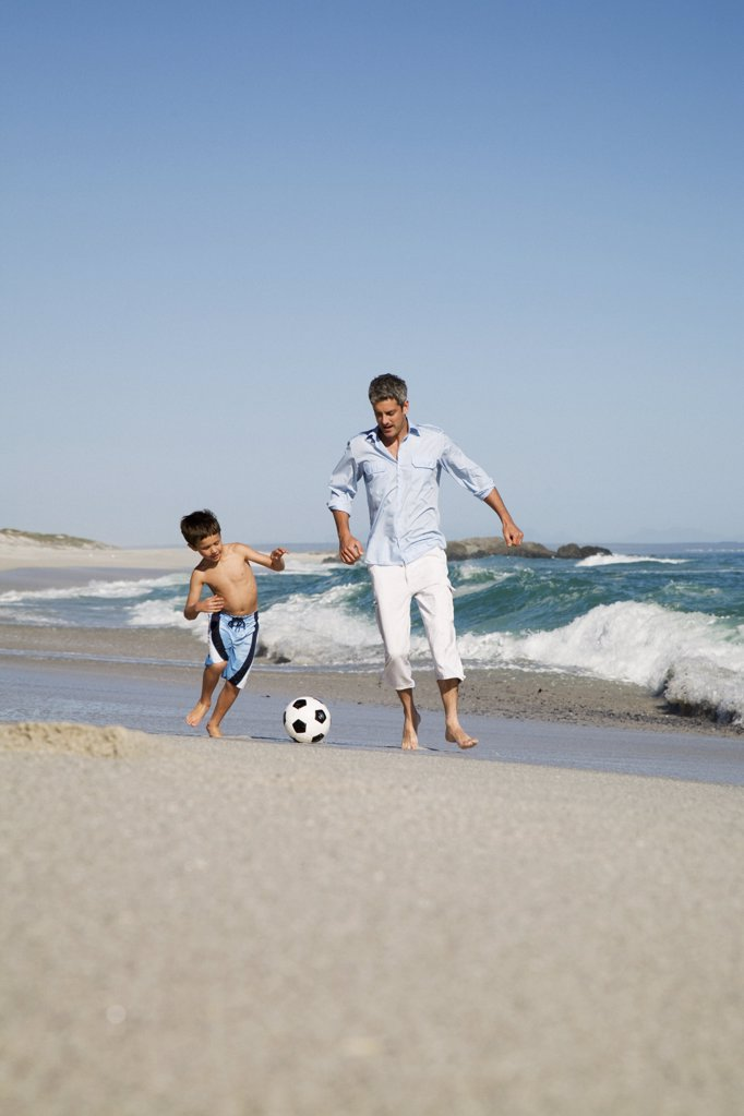 Father and son playing football by the sea : Stock Photo