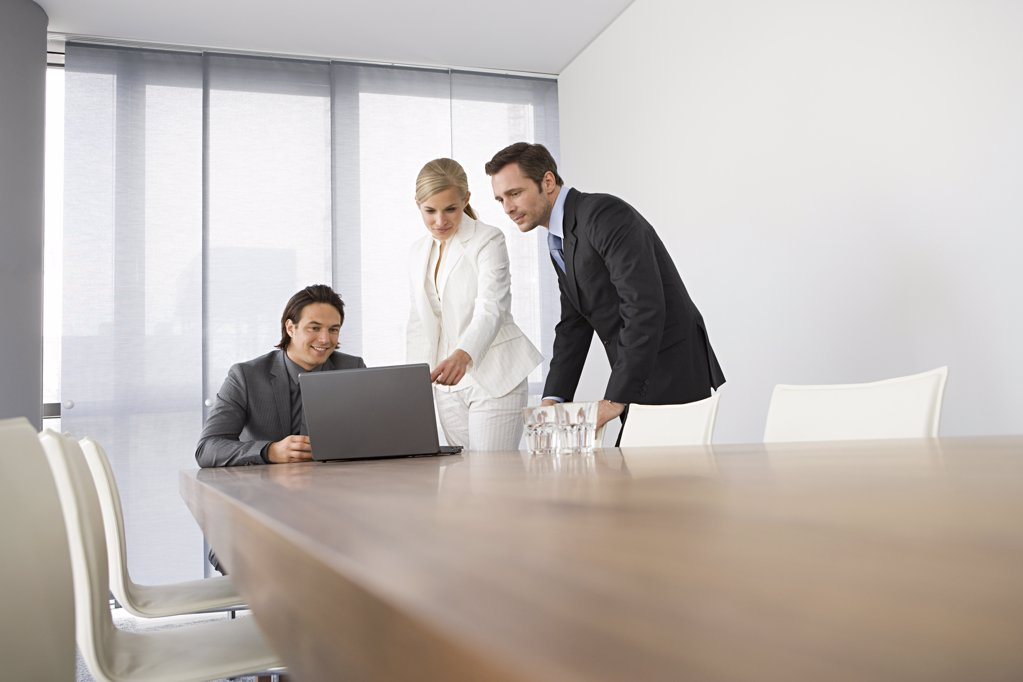 Colleagues looking at laptop : Stock Photo