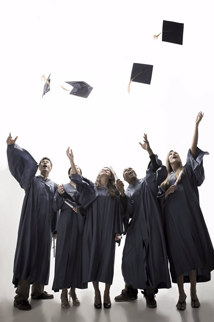 Stock Photo: 1439R-1110557 Graduates throwing mortarboards