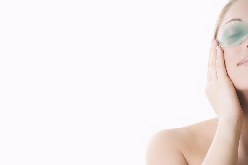 Stock Photo: 1439R-1111294 Woman using eye mask