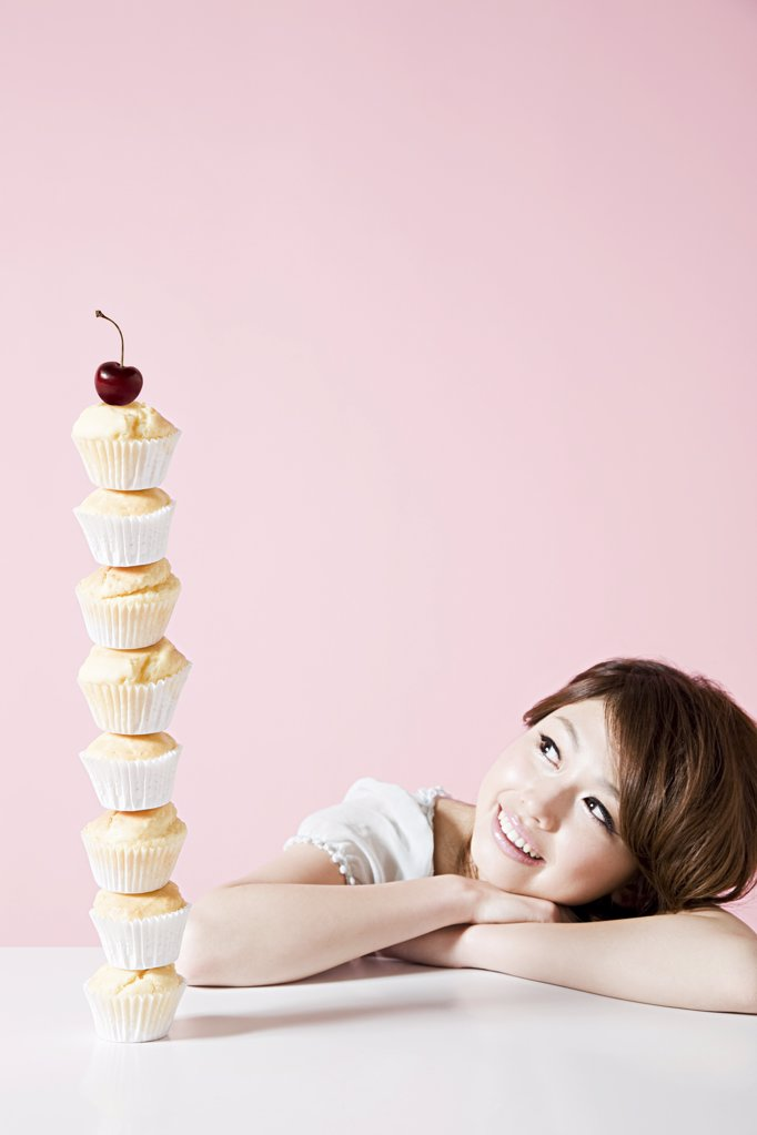 Woman looking at stack of cakes : Stock Photo