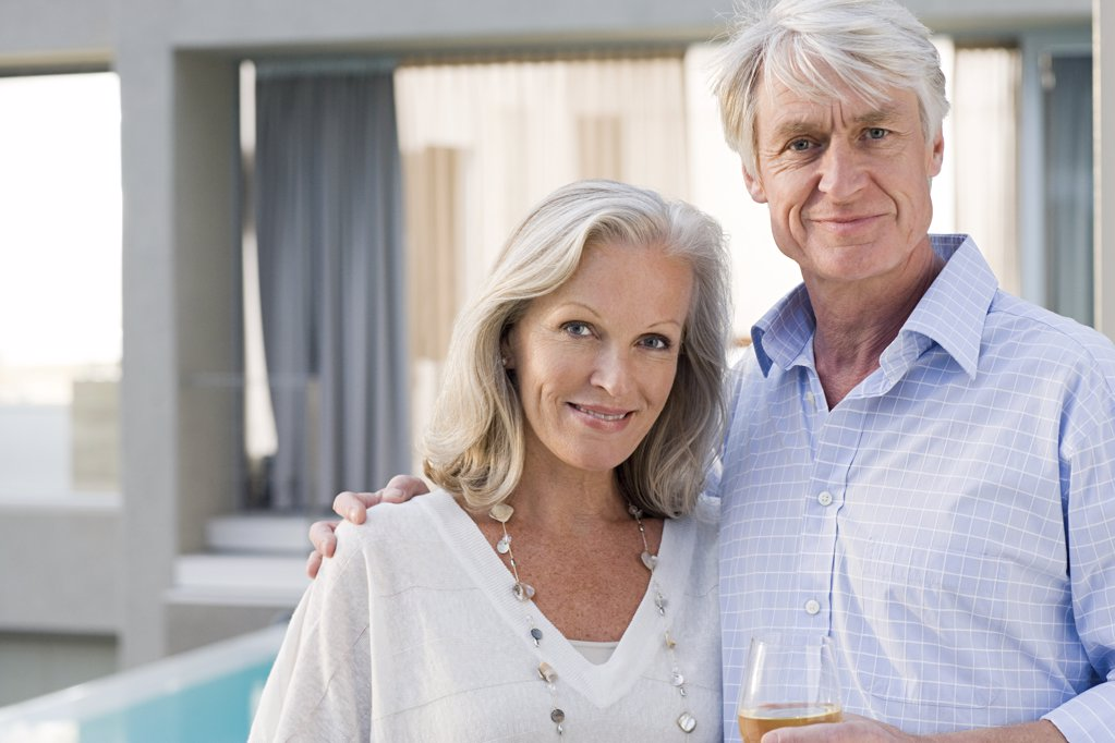 Middle aged couple standing outside house : Stock Photo