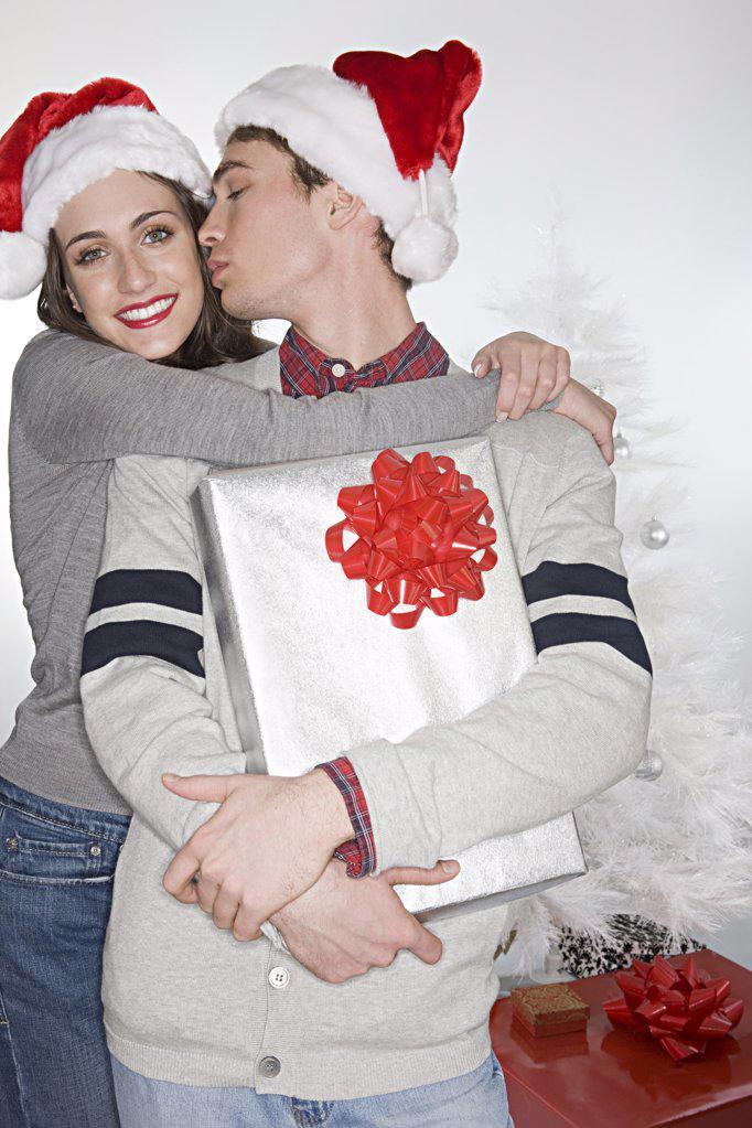 Stock Photo: 1439R-1113825 Couple in santa hats kissing