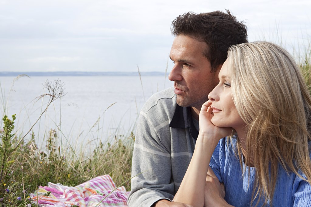 Couple outdoors looking towards sea : Stock Photo