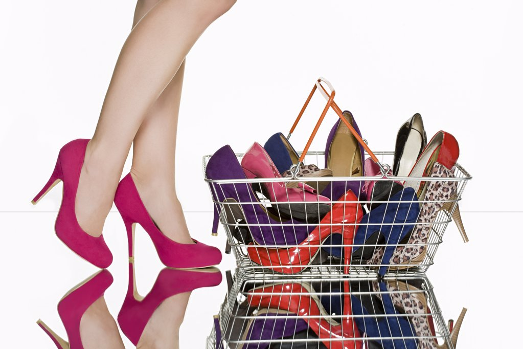 Legs of woman and shopping basket full of shoes : Stock Photo