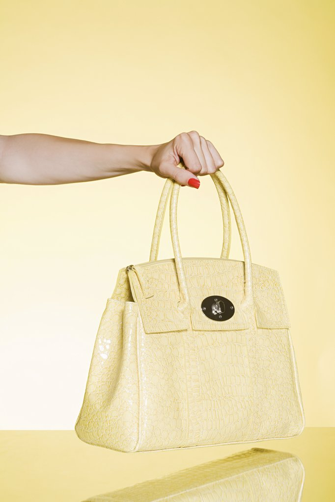 Stock Photo: 1439R-1117852 Woman holding yellow handbag