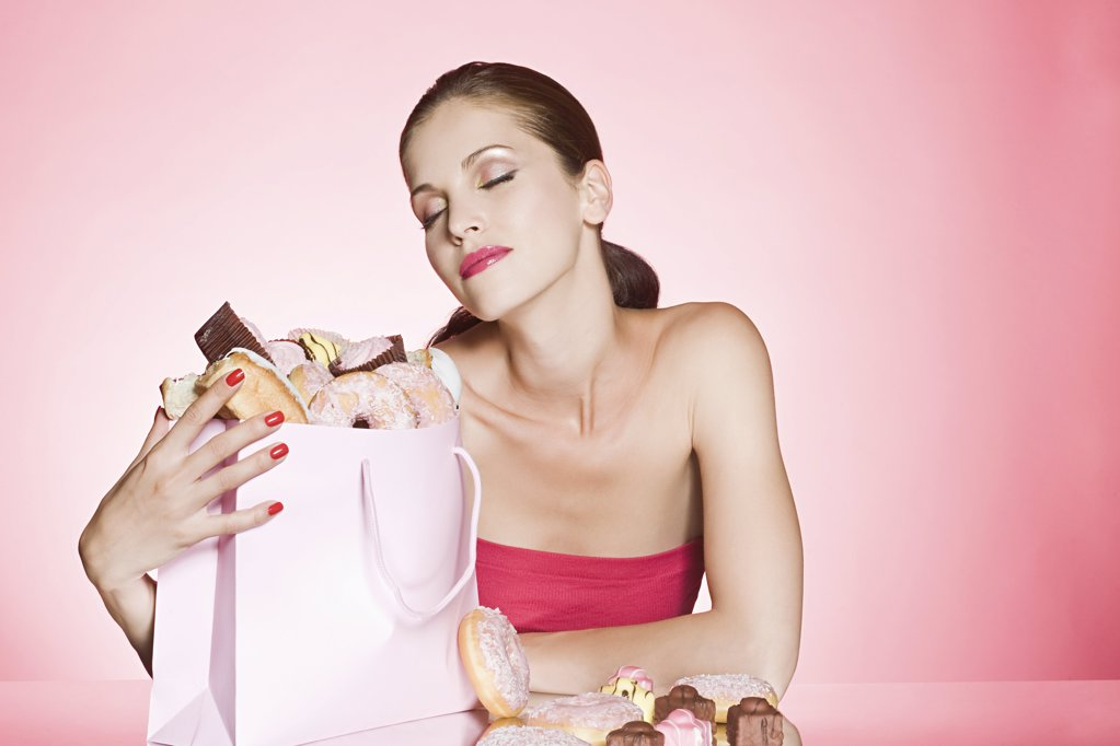 Stock Photo: 1439R-1117854 Young woman with bag of cakes and donuts