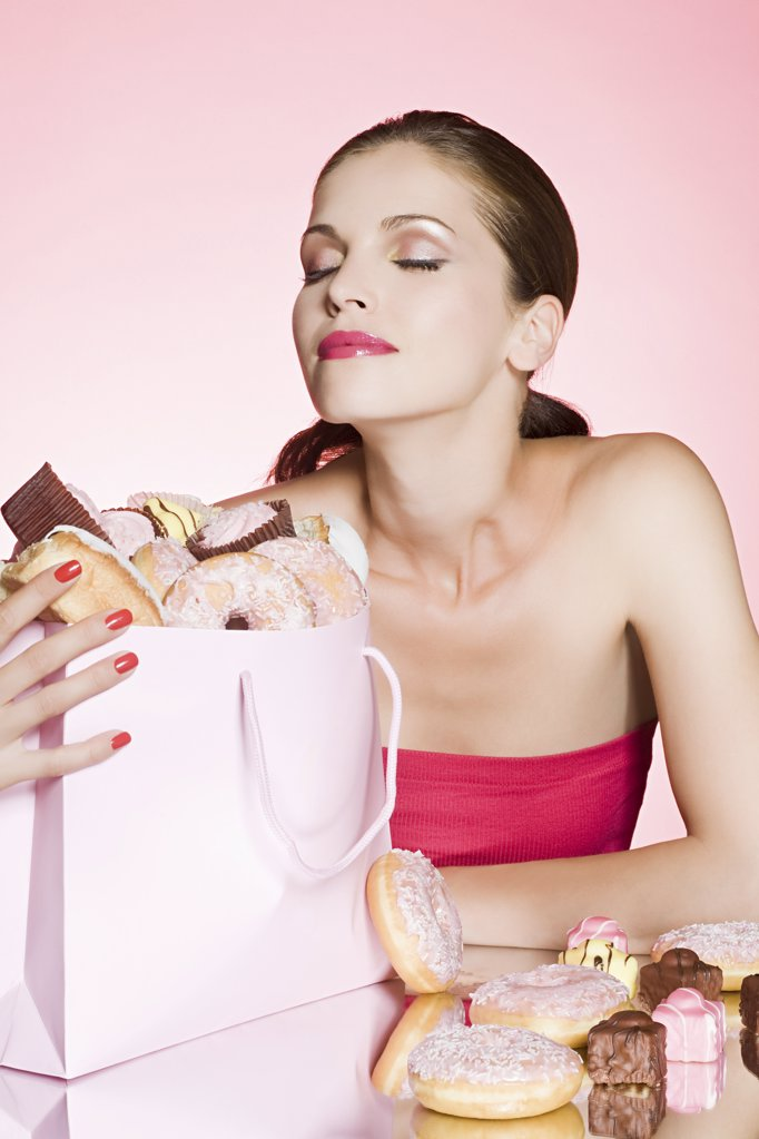 Young woman with bag of cakes and donuts : Stock Photo