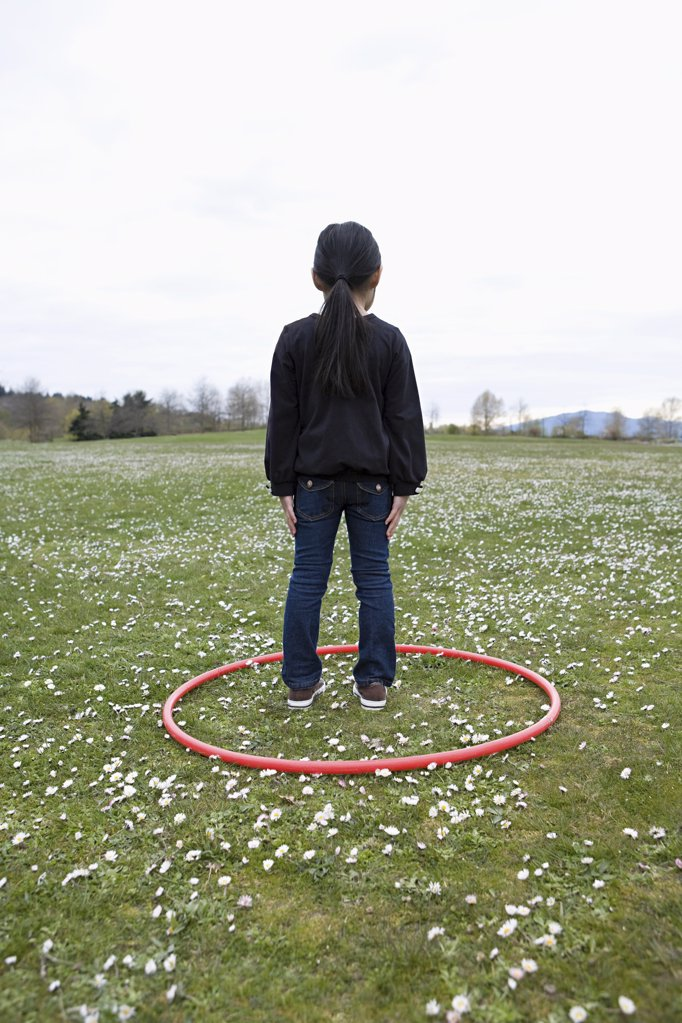 Girl standing in a hoop in a field : Stock Photo