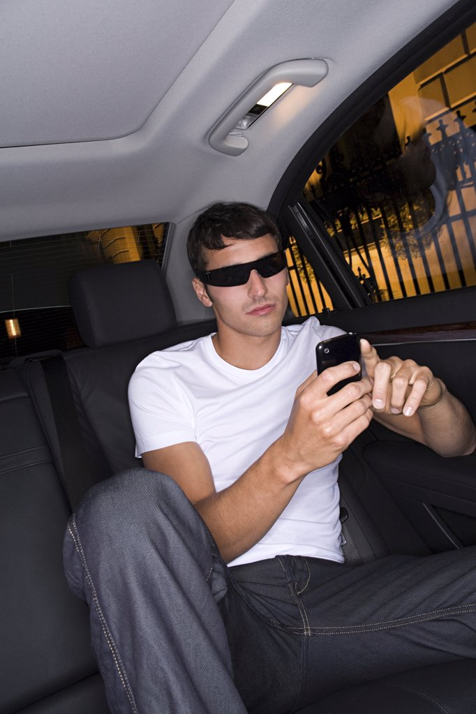 Cool man text messaging in car : Stock Photo