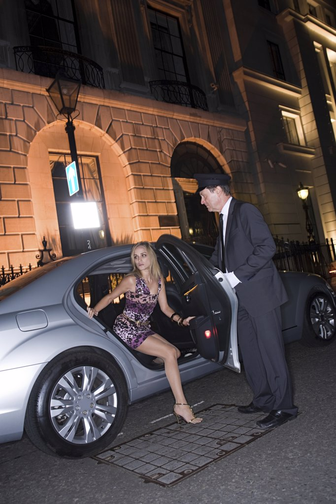 Stock Photo: 1439R-1118218 Wealthy woman getting out of car