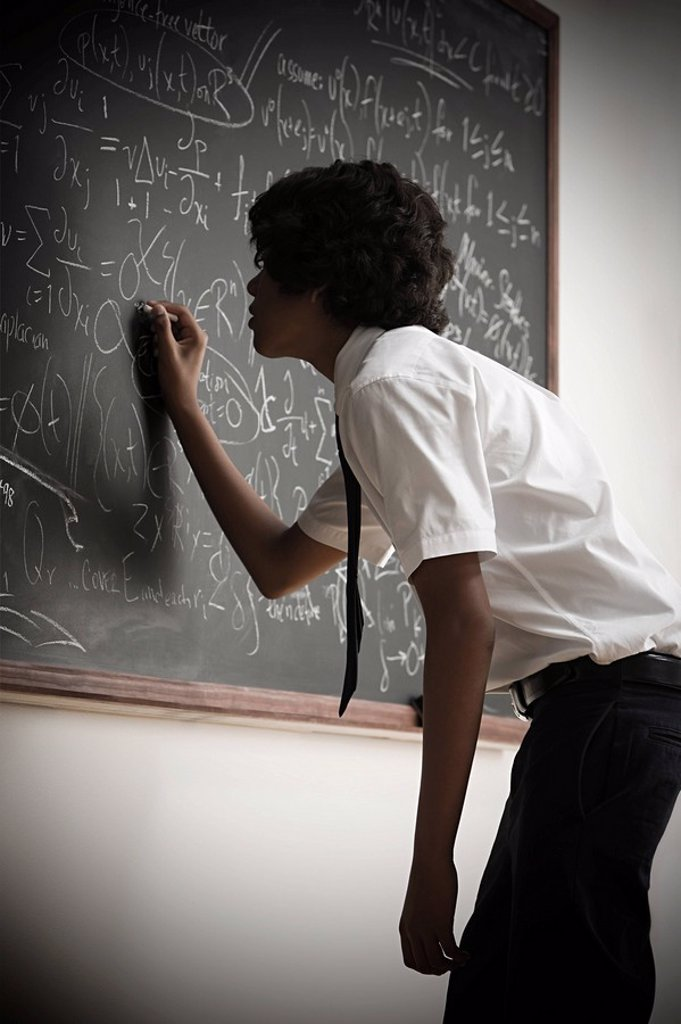 Stock Photo: 1439R-1118407 Boy writing on blackboard