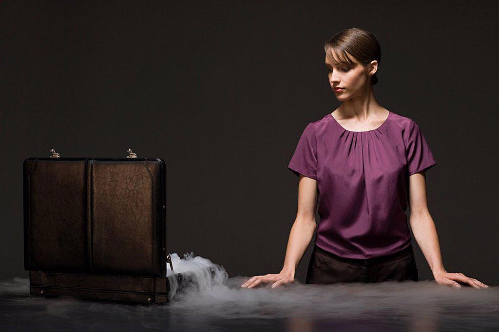 Stock Photo: 1439R-1118501 Woman with smoking briefcase