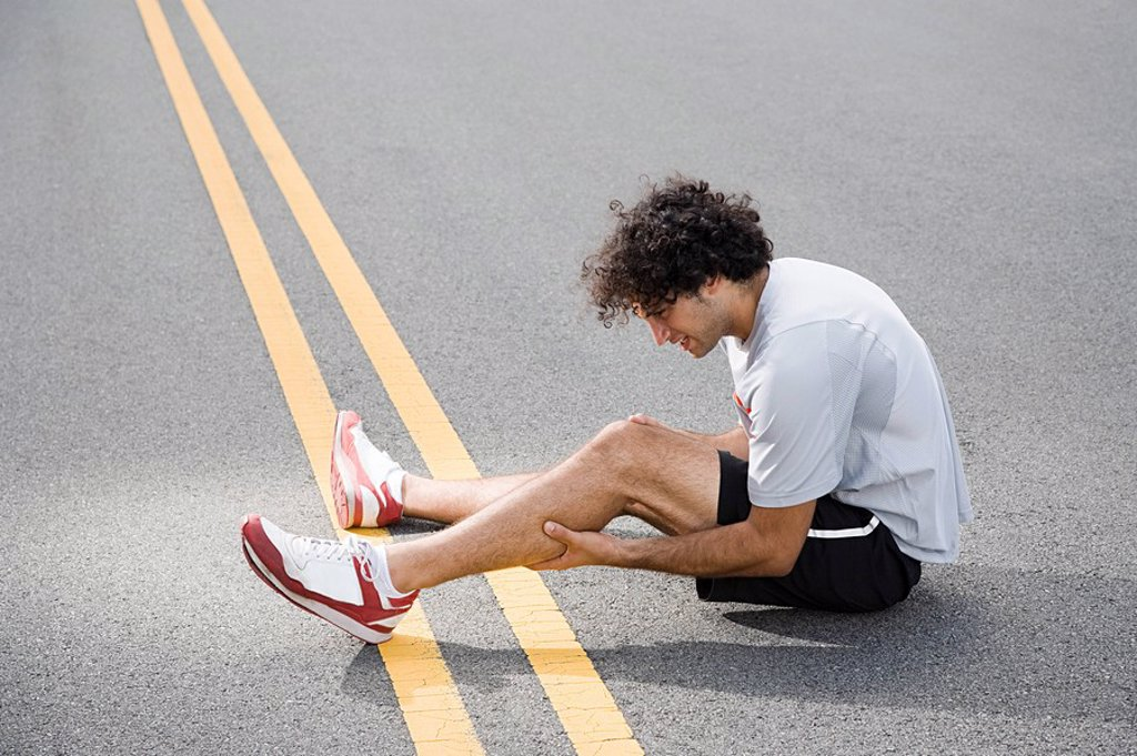 Stock Photo: 1439R-1118773 Runner with injured leg
