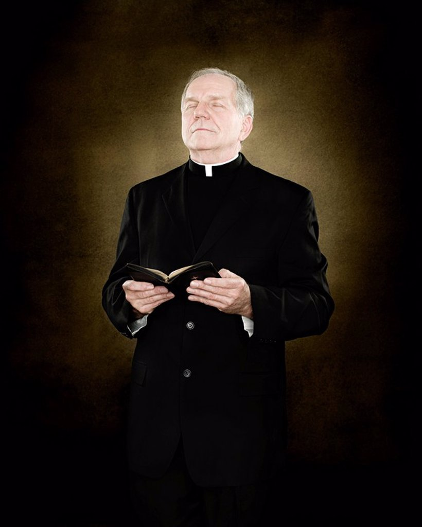 A priest holding a bible : Stock Photo