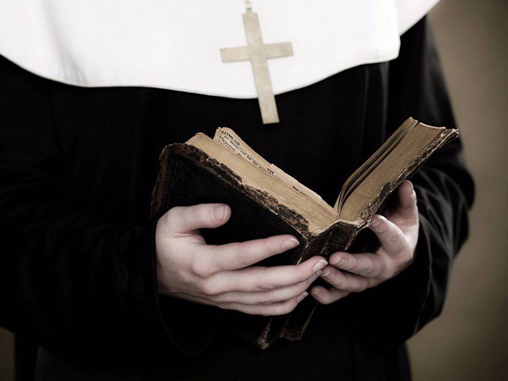 A nun holding a bible : Stock Photo
