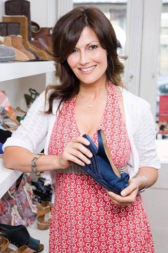 Woman holding shoe in store : Stock Photo
