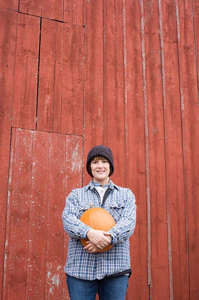 Stock Photo: 1439R-1120857 Female farmer holding a pumpkin