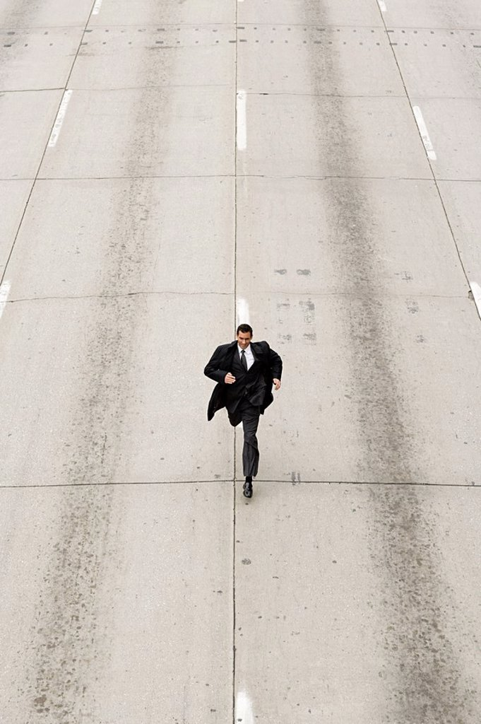 Looking down to a businessman running down a road : Stock Photo