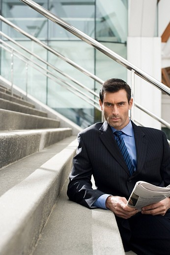 A businessman leaning on steps with a newspaper : Stock Photo