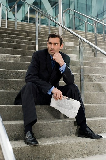 A businessman sitting on steps with a newspaper : Stock Photo