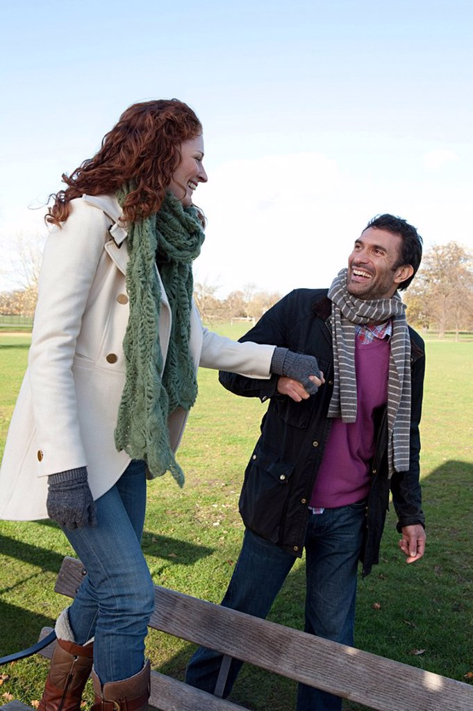 A woman walking on a park bench whilst holding hands with her partner : Stock Photo
