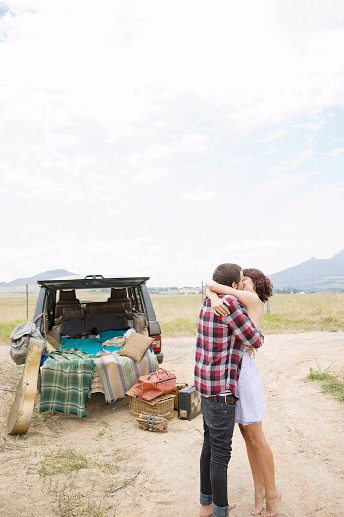 Couple kissing by suv : Stock Photo