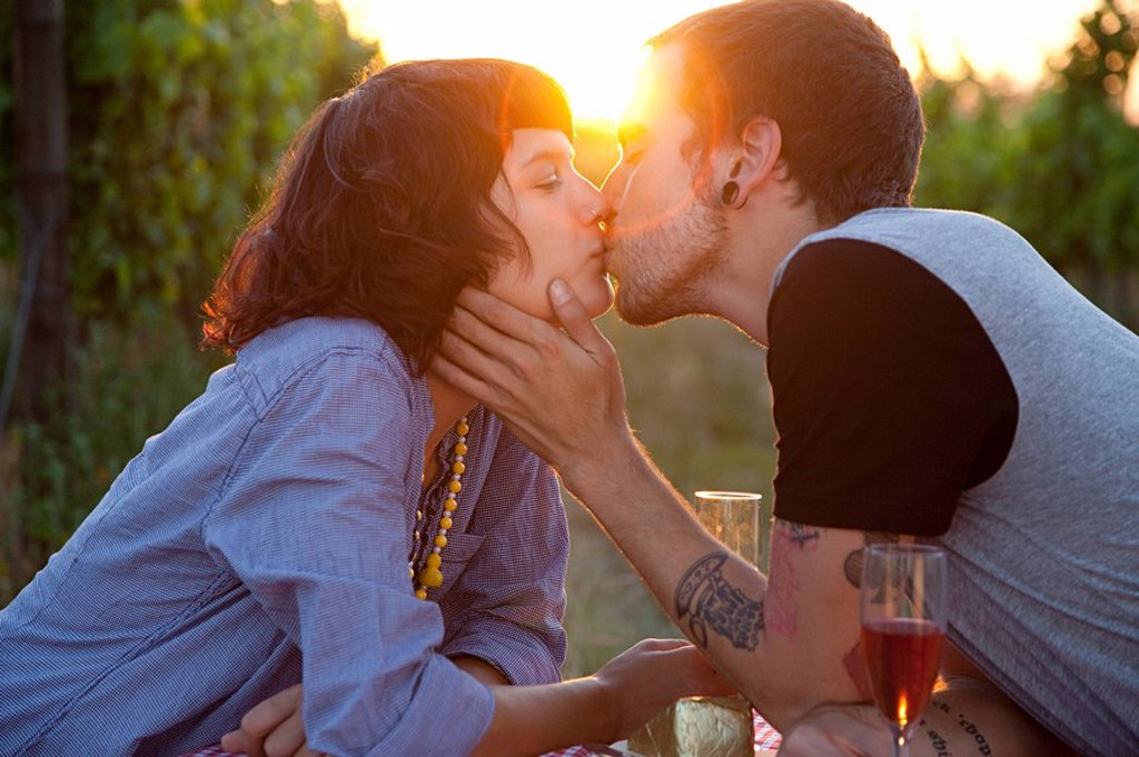 Stock Photo: 1439R-1122055 Couple kissing at sunset