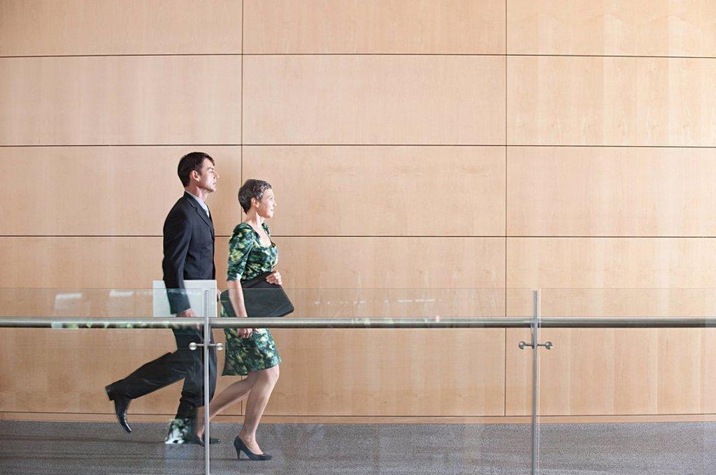 Businesspeople running through corridor : Stock Photo
