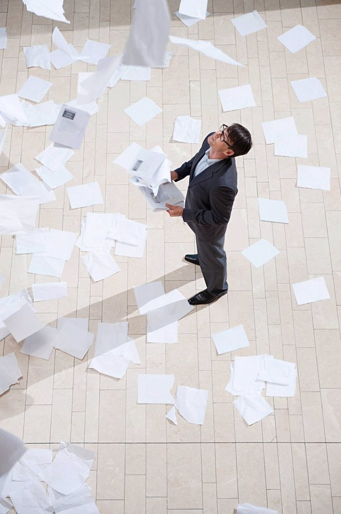 Businessman throwing papers : Stock Photo