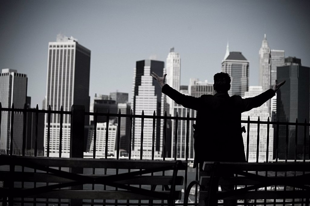 Stock Photo: 1439R-1122629 Man with arms open and view of lower manhattan
