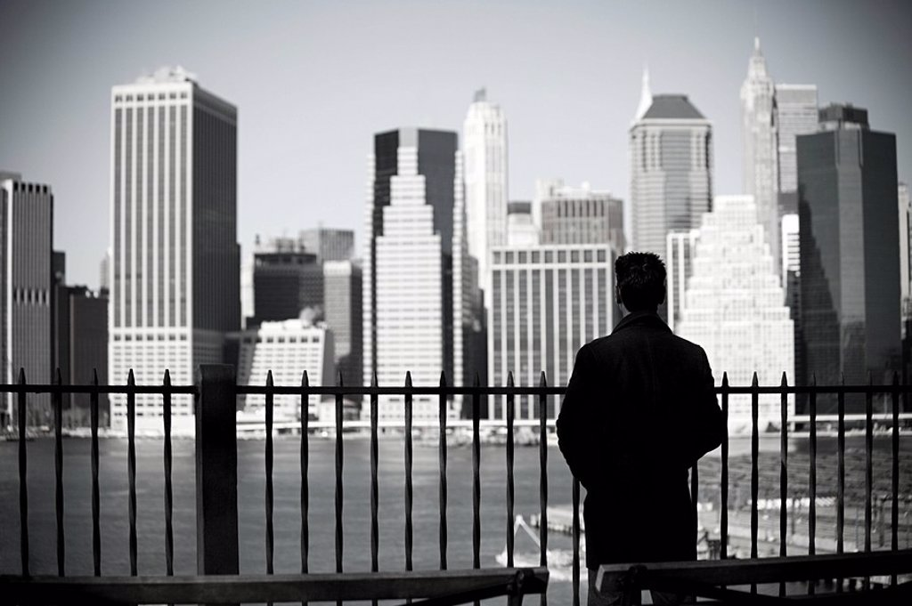 Man looking to lower manhattan from brooklyn heights promenade : Stock Photo