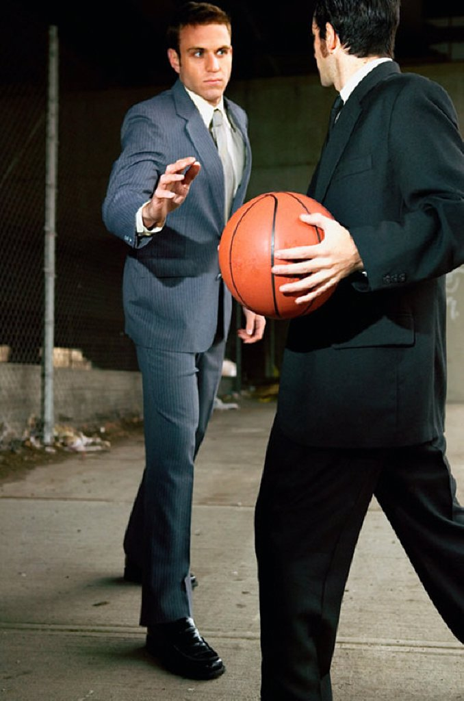 Businessmen playing basketball : Stock Photo