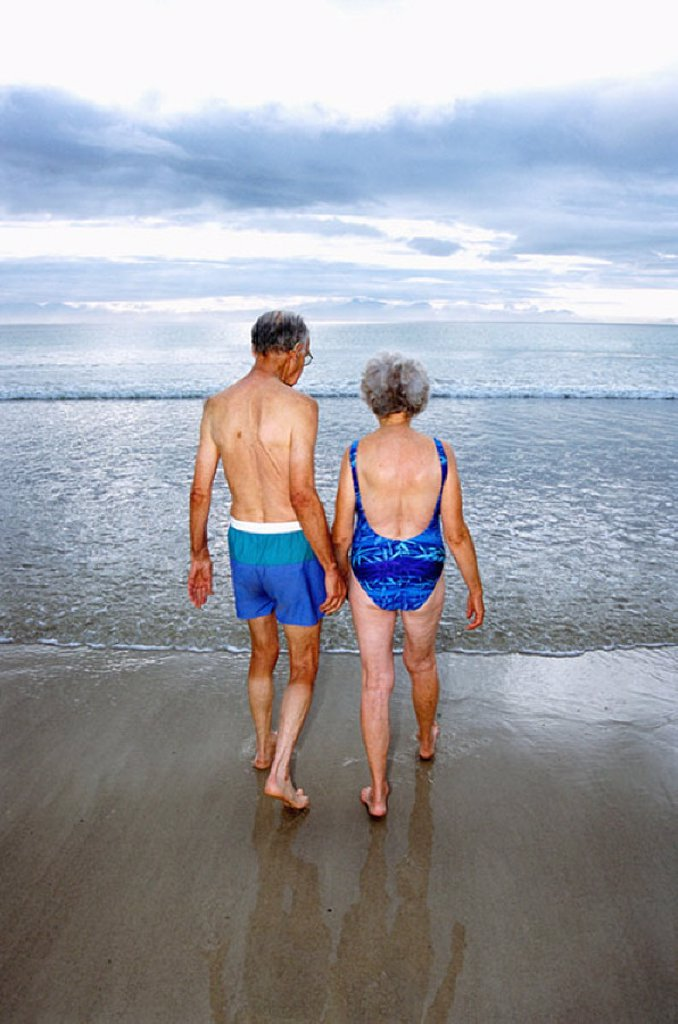 Stock Photo: 1439R-1124358 A mature couple going for a swim on the beach